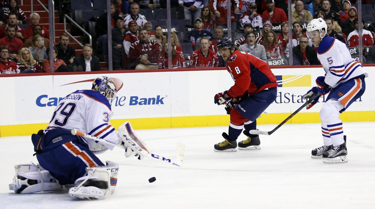 Edmonton Oilers goalie Anders Nilsson (39), from Sweden, deflects a shot by Washington Capitals left wing Alex Ovechkin (8), from Russia, with Oilers defenseman Mark Fayne (5) defending, in the third period of an NHL hockey game, Monday, Nov. 23, 2015, in