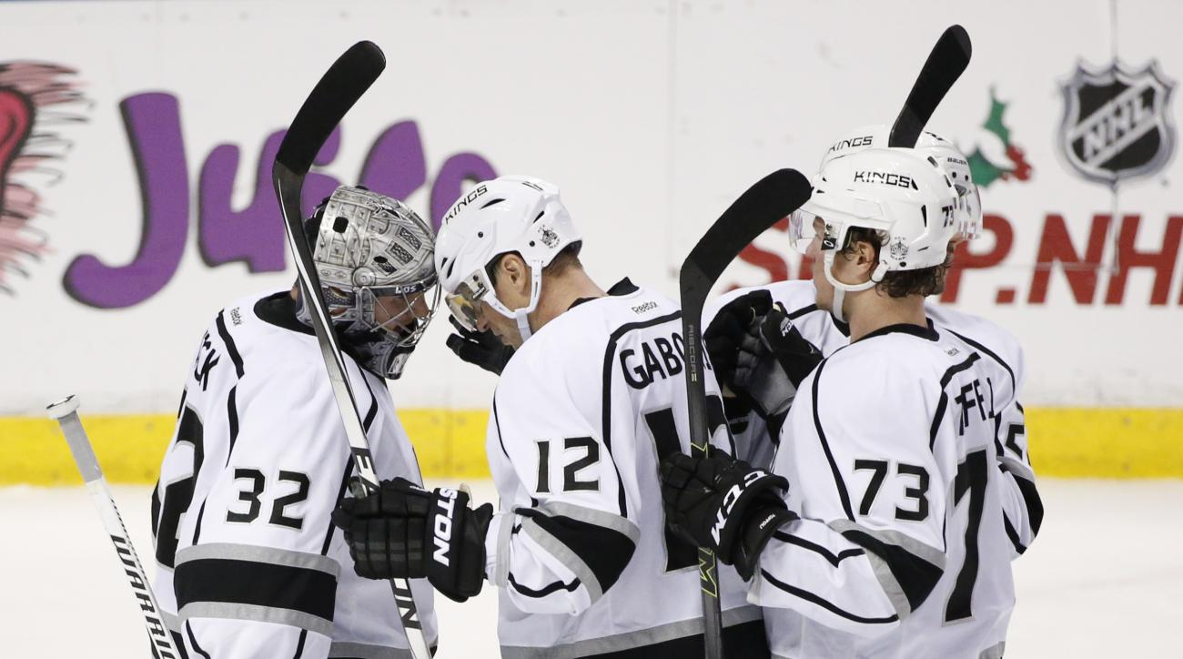Los Angeles Kings goalie Jonathan Quick (32), right wing Marian Gaborik (12) and center Tyler Toffoli (73) celebrate after the Kings defeated the Florida Panthers 3-1 in an NHL hockey game, Monday, Nov. 23, 2015 in Sunrise, Fla. (AP Photo/Wilfredo Lee)