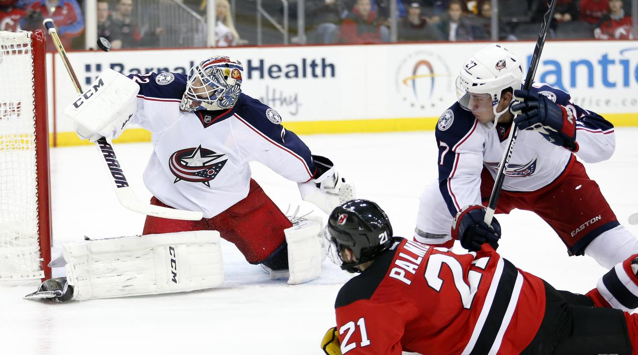 Columbus Blue Jackets goalie Sergei Bobrovsky, left, of Russia, tries to deflect a shot by New Jersey Devils right wing Kyle Palmieri (21) as Blue Jackets defenseman Ryan Murray (27) helps protect the net during the second period of an NHL hockey game, We