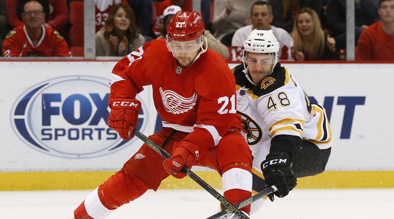 Boston Bruins defenseman Colin Miller (48) defends against Detroit Red Wings left wing Tomas Tatar (21) in overtime of an NHL hockey game Wednesday, Nov. 25, 2015, in Detroit. Boston won 3-2. (AP Photo/Paul Sancya)