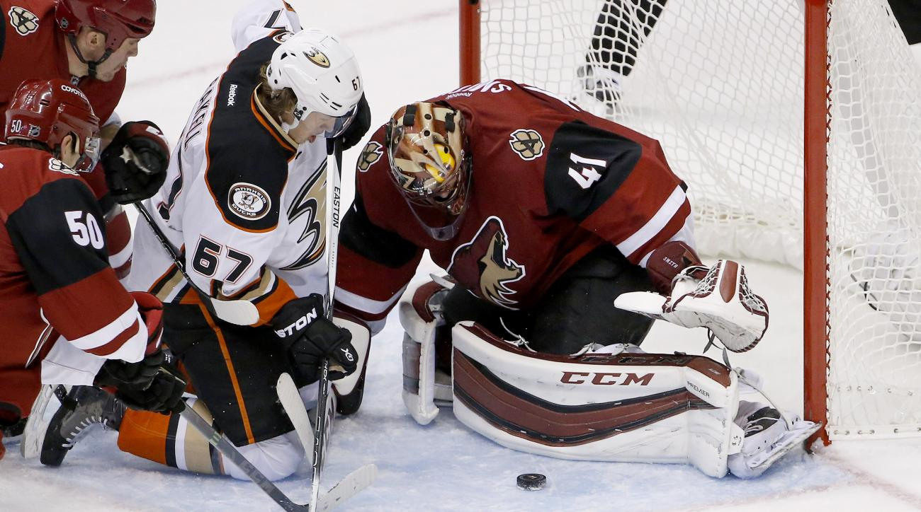 Arizona Coyotes' Mike Smith (41) makes a save on a shot by Anaheim Ducks' Rickard Rakell (67), of Sweden, as Coyotes' Antoine Vermette (50) defends during the second period of an NHL hockey game Wednesday, Nov. 25, 2015, in Glendale, Ariz. (AP Photo/Ross