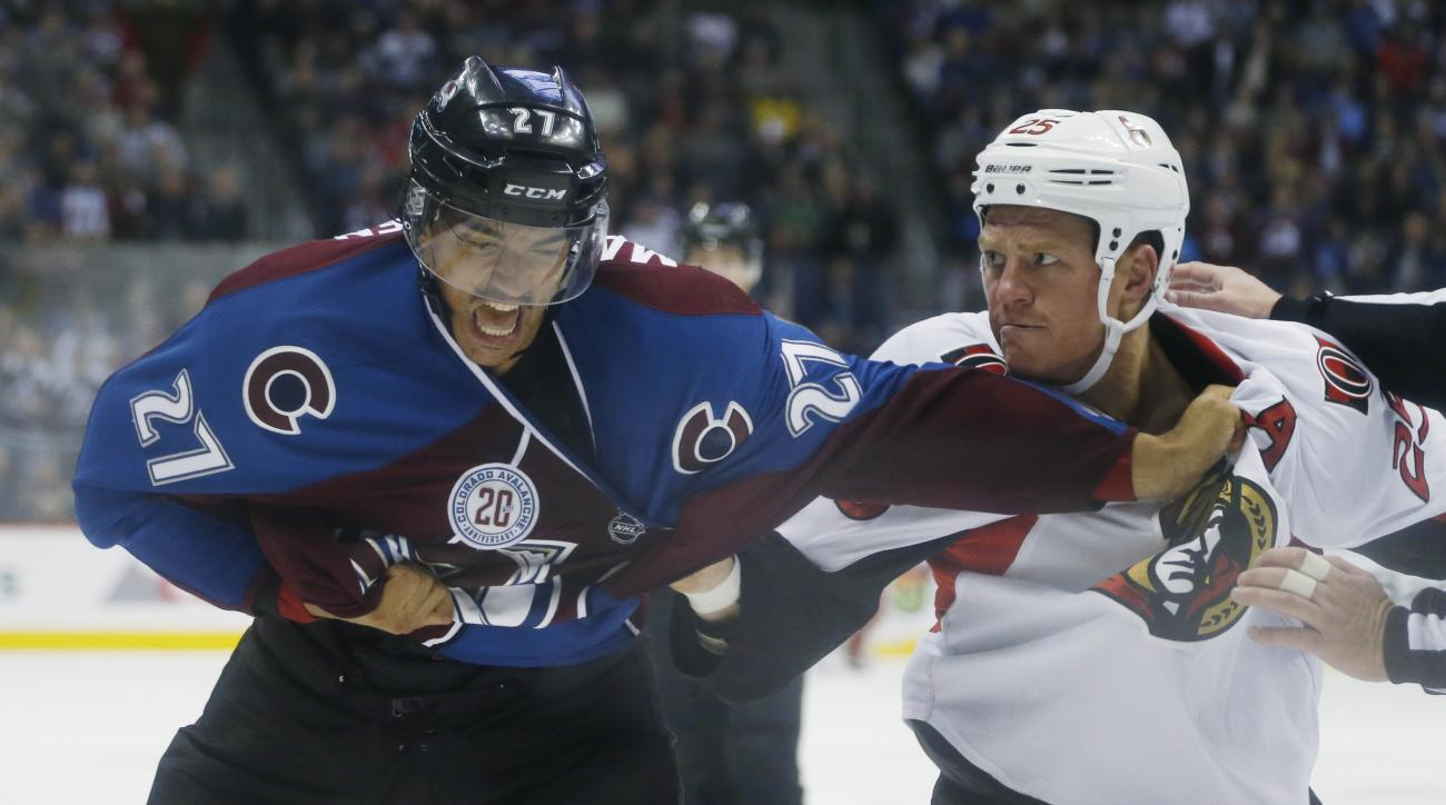 Colorado Avalanche center Andreas Martinsen, left, of Norway, reacts after getting hit by a punch thrown by Ottawa Senators right wing Chris Neil during the third period of an NHL hockey game Wednesday, Nov. 25, 2015, in Denver. Ottawa won 5-3. (AP Photo/