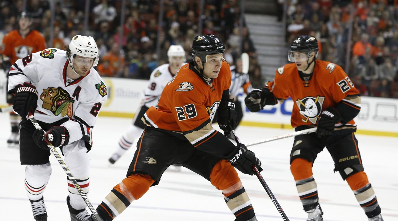 Anaheim Ducks right wing Chris Stewart (29) passes the puck ahead as Chicago Blackhawks' Duncan Keith, left, defends during the second period of an NHL hockey game in Anaheim, Calif., Friday, Nov. 27, 2015. (AP Photo/Christine Cotter)