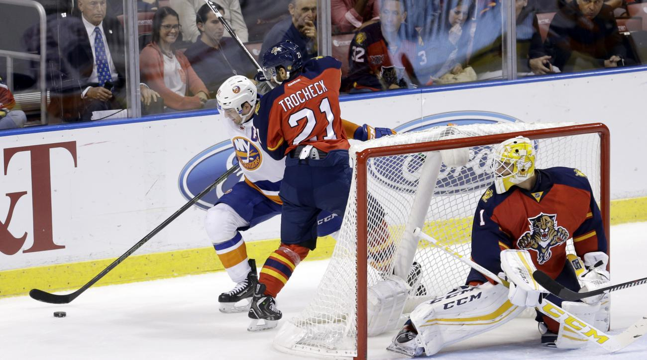 Florida Panthers center Vincent Trocheck (21) checks New York Islanders center John Tavares (91) during the second period of an NHL hockey game, Friday, Nov. 27, 2015, in Sunrise, Fla. (AP Photo/Alan Diaz)