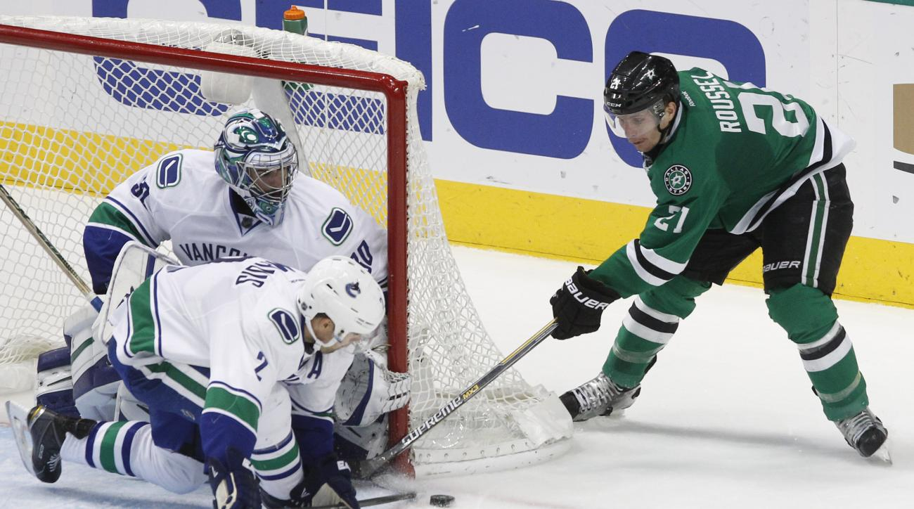Vancouver Canucks defenseman Dan Hamhuis (2) blocks the puck against Dallas Stars left wing Antoine Roussel (21) as goalie Ryan Miller (30) watches during the second period of an NHL hockey game Friday, Nov. 27, 2015, in Dallas.  (AP Photo/Tim Sharp)