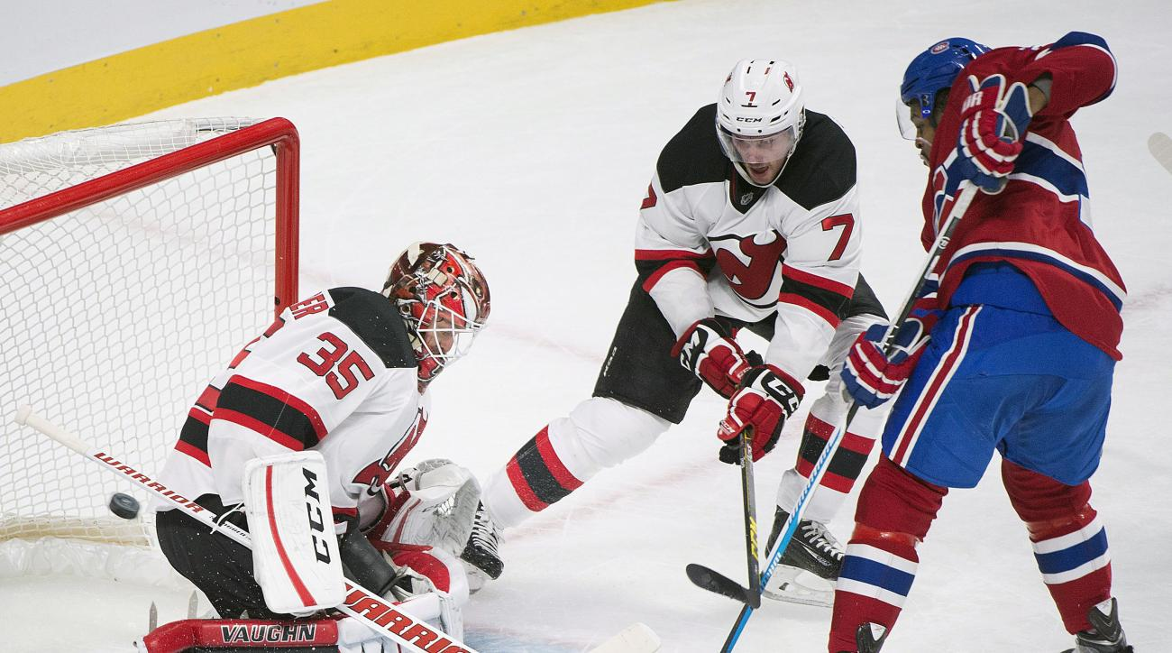 New Jersey Devils' goalie Cory Schneider makes a save against Montreal Canadiens' Devante Smith-Pelly, right, as the Devils' Jon Merrill (7) defends during the first period of an NHL hockey game, in Montreal, Saturday, Nov. 28, 2015. (Graham Hughes/The Ca
