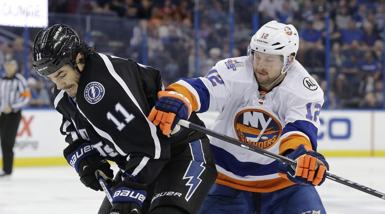 Tampa Bay Lightning center Brian Boyle (11) is hit by New York Islanders left wing Josh Bailey (12) as he goes after the puck during the second period of an NHL hockey game Saturday, Nov. 28, 2015, in Tampa, Fla. (AP Photo/Chris O'Meara)