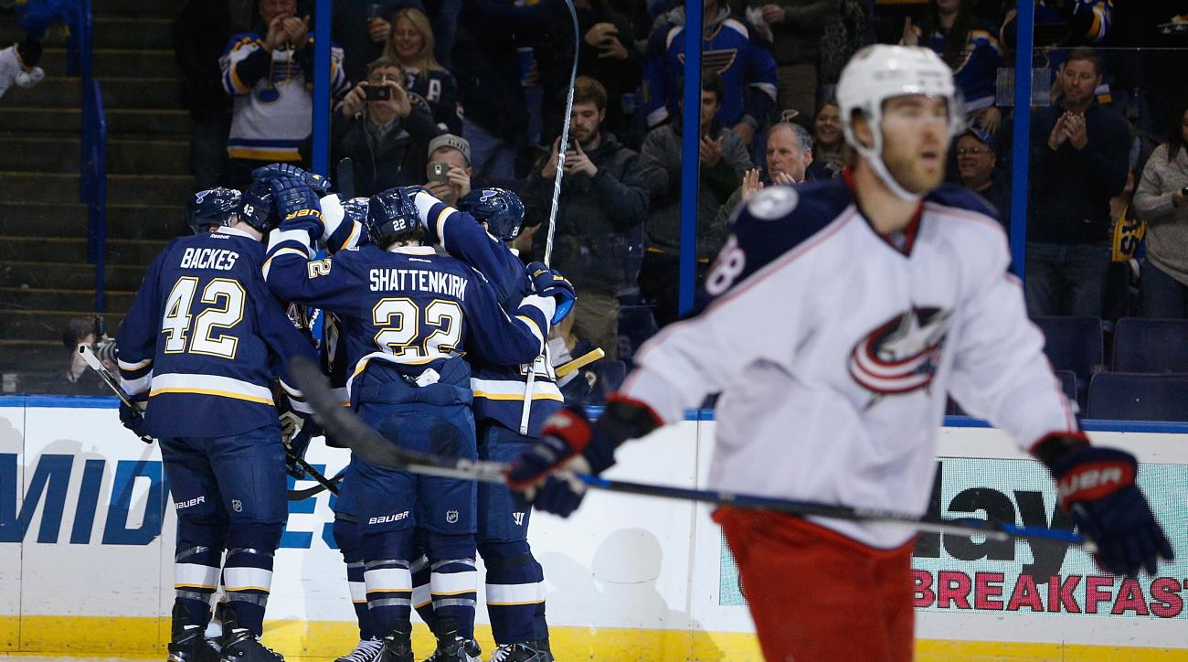 Columbus Blue Jackets' David Savard, right, skates off as members of the St. Louis Blues celebrate after scoring a goal during the second period of an NHL hockey game Saturday, Nov. 28, 2015, in St. Louis. (AP Photo/Scott Kane)