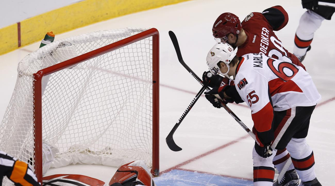 Arizona Coyotes left wing Mikkel Boedker scores on Ottawa Senators goalie Craig Anderson (41) as defenseman Erik Karlsson (65) defends in the second period during an NHL hockey game, Saturday, Nov. 28, 2015, in Glendale, Ariz. (AP Photo/Rick Scuteri)