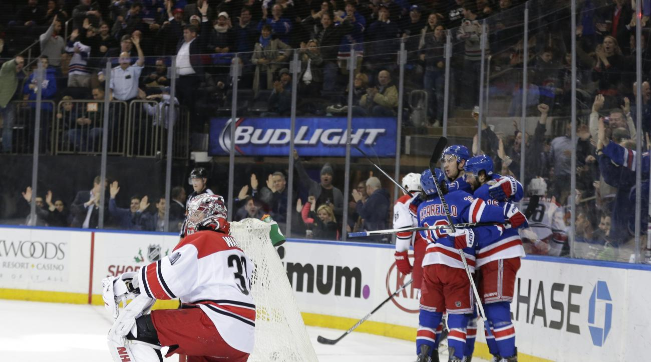 Carolina Hurricanes' Cam Ward (30) reacts as the New York Rangers celebrator a goal by Derick Brassard, right, during the second period of an NHL hockey game, Monday, Nov. 30, 2015, in New York. (AP Photo/Frank Franklin II)