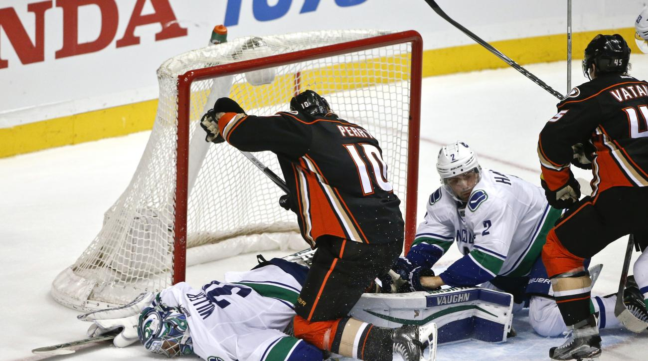 Anaheim Ducks right wing Corey Perry uses his knee to pin down Vancouver Canucks goalie Ryan Miller as Canucks defenseman Dan Hamhuis covers the puck during the second period of a NHL hockey game Monday, Nov. 30, 2015, in Anaheim, Calif.  (AP Photo/Lenny