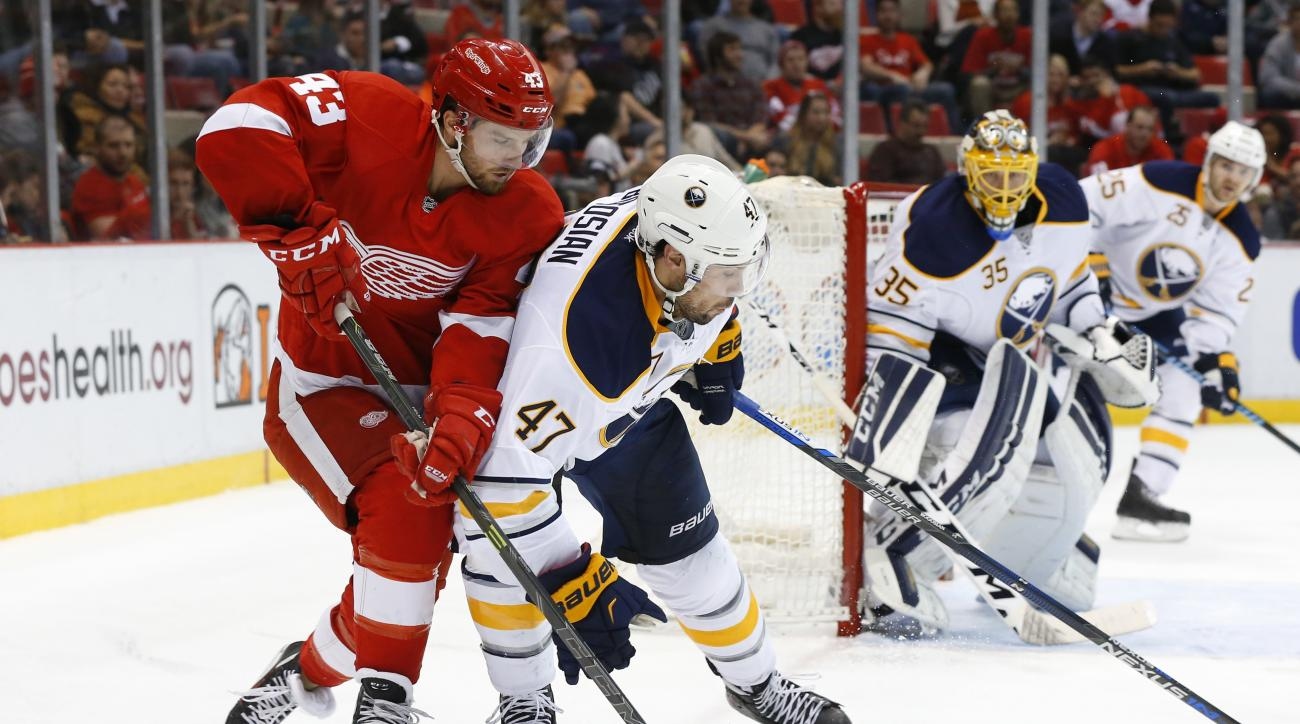 Detroit Red Wings center Darren Helm (43) and Buffalo Sabres defenseman Zach Bogosian (47) battle for the puck in the second period of an NHL hockey game Tuesday, Dec. 1, 2015 in Detroit. (AP Photo/Paul Sancya)