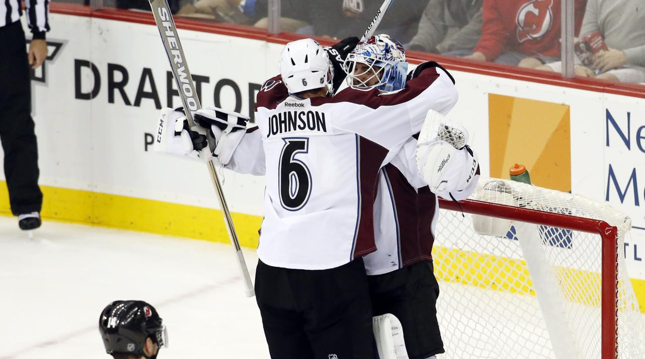 Colorado Avalanche defenseman Erik Johnson (6) and goalie Reto Berra, of Germany, celebrate as New Jersey Devils center Adam Henrique (14) skates away at the end of an NHL hockey game, Tuesday, Dec. 1, 2015, in Newark, N.J. The Avalanche won 2-1. (AP Phot