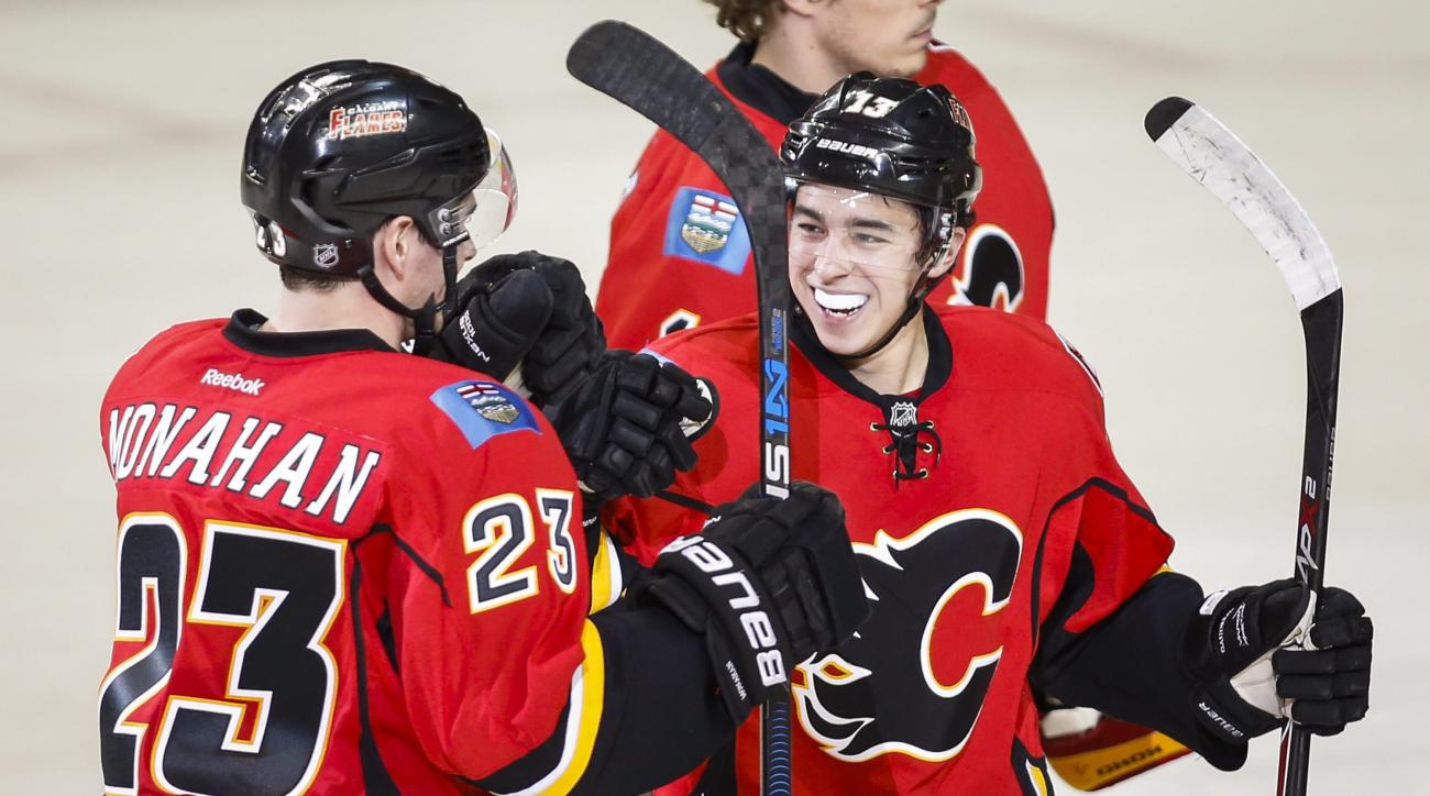 Calgary Flames' Sean Monahan, left, celebrates his game-winning goal against the Dallas Stars with teammate Johnny Gaudreau in an overtime shootout in an NHL hockey game in Calgary, Alberta, Tuesday, Dec. 1, 2015. (Jeff McIntosh/The Canadian Press via AP)