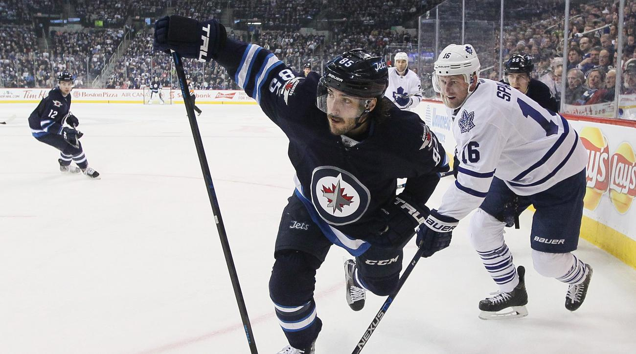 Winnipeg Jets' Mathieu Perreault (85) and Toronto Maple Leafs' Nick Spaling (16) skate for the puck deep in the corner during second period NHL action, Wednesday, Dec. 2, 2015, in Winnipeg, Manitoba. (John Woods/The Canadian Press via AP) MANDATORY CREDIT