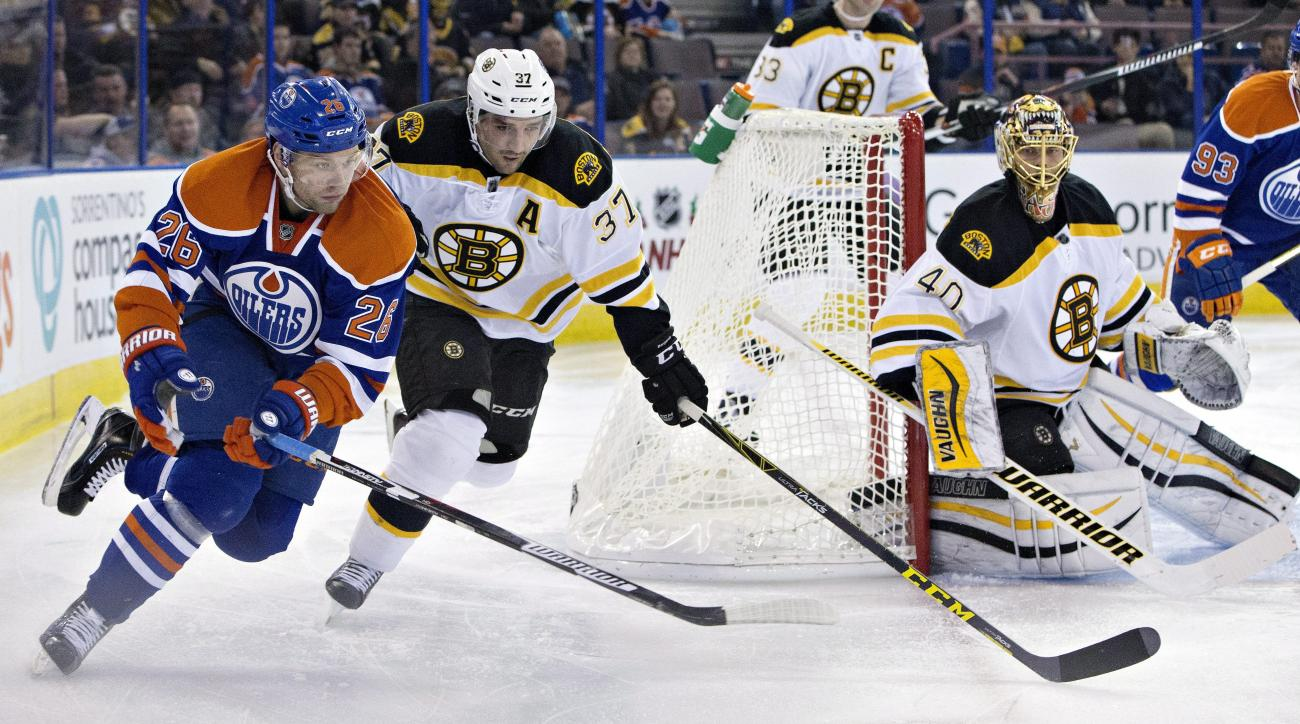 Boston Bruins' Patrice Bergeron (37) and Edmonton Oilers' Iiro Pakarinen (26) chase the rebound from goalie Tuukka Rask (40) during the second period of an NHL hockey game, Wednesday, Dec. 2, 2015, in Edmonton, Alberta. (Jason Franson/The Canadian Press v