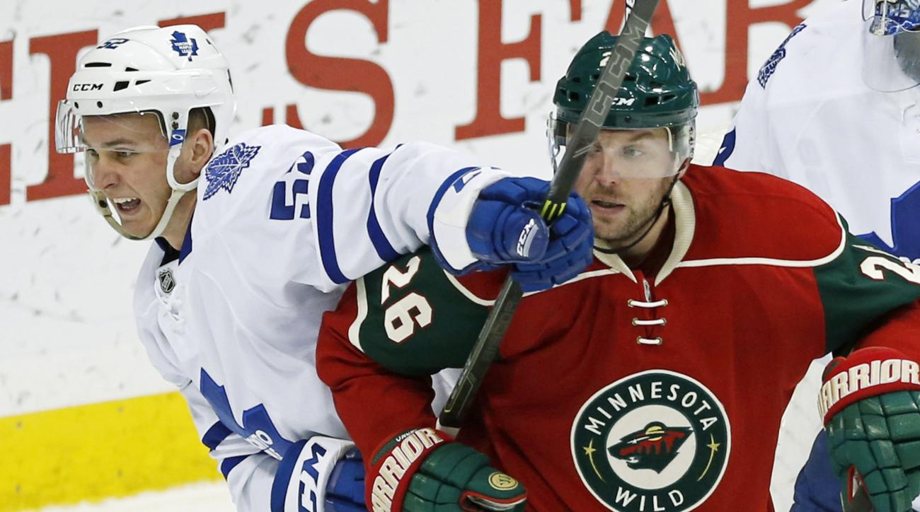 Minnesota Wild's Thomas Vanek right, of Austria, gets a glove on the stick of Toronto Maple Leafs' Martin Marincin, of Slovakia, during the first period of an NHL hockey game, Thursday, Dec. 3, 2015, in St. Paul, Minn. (AP Photo/Jim Mone)