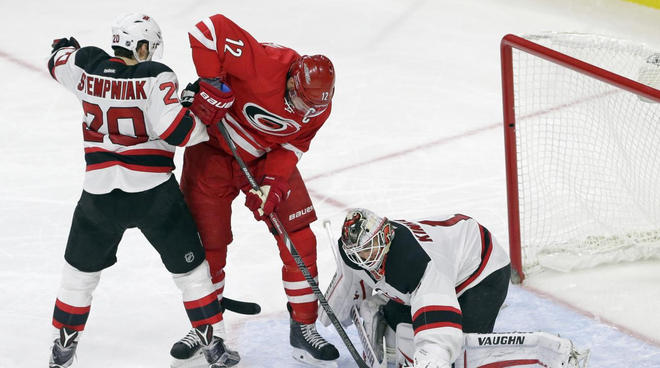 Carolina Hurricanes' Eric Staal (12) tries to score as New Jersey Devils' Lee Stempniak (20) and goalie Keith Kinkaid defend during the third period of an NHL hockey game in Raleigh, N.C., Thursday, Dec. 3, 2015. New Jersey won 5-1. (AP Photo/Gerry Broome