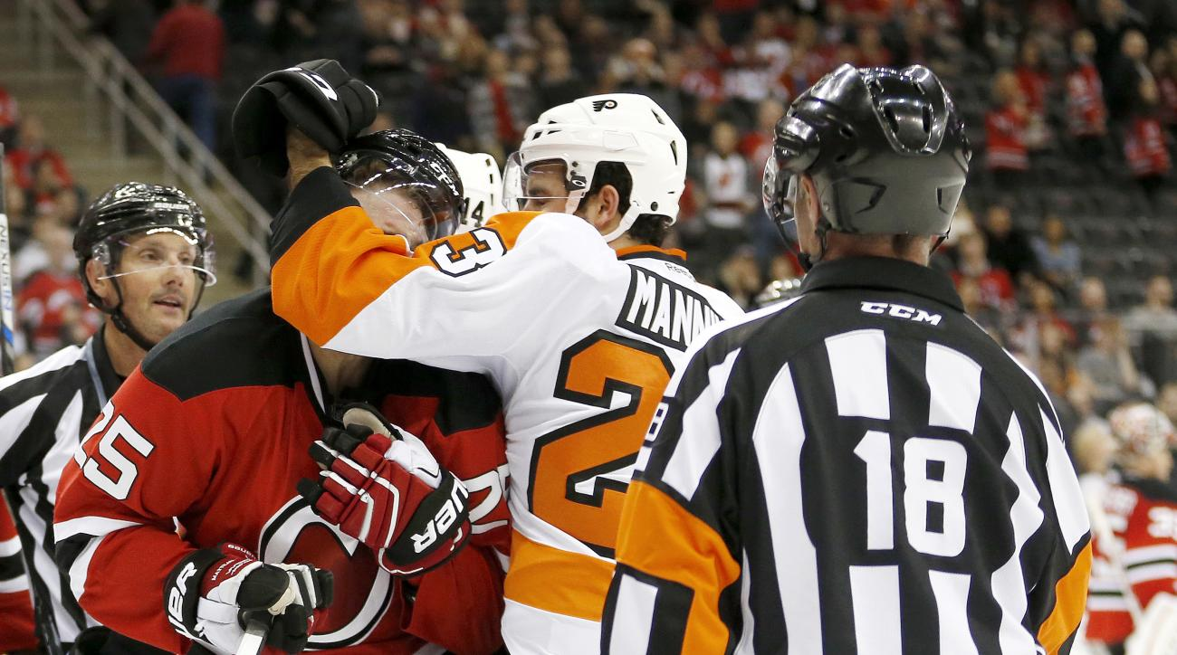 Philadelphia Flyers defenseman Brandon Manning, center right, and New Jersey Devils center Stefan Matteau (25) scuffle as official Greg Kimmerly (18) watches during the first period of an NHL hockey game Friday, Dec. 4, 2015, in Newark, N.J. (AP Photo/Jul