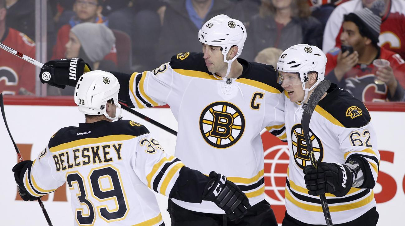 Boston Bruins' Zdeno Charo, center, from Slovakia, celebrates his goal against the Calgary Flames with teammates Matt Beleskey, left, and Zach Trotman during the second period of an NHL hockey game Friday, Dec. 4, 2015, in Calgary, Alberta. (Larry MacDoug