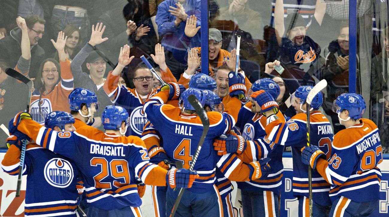 Edmonton Oilers celebrate a 2-1 win in overtime over the Dallas Stars in an NHL hockey game Friday, Dec. 4, 2015, in Edmonton, Alberta. (Jason Franson/The Canadian Press via AP)