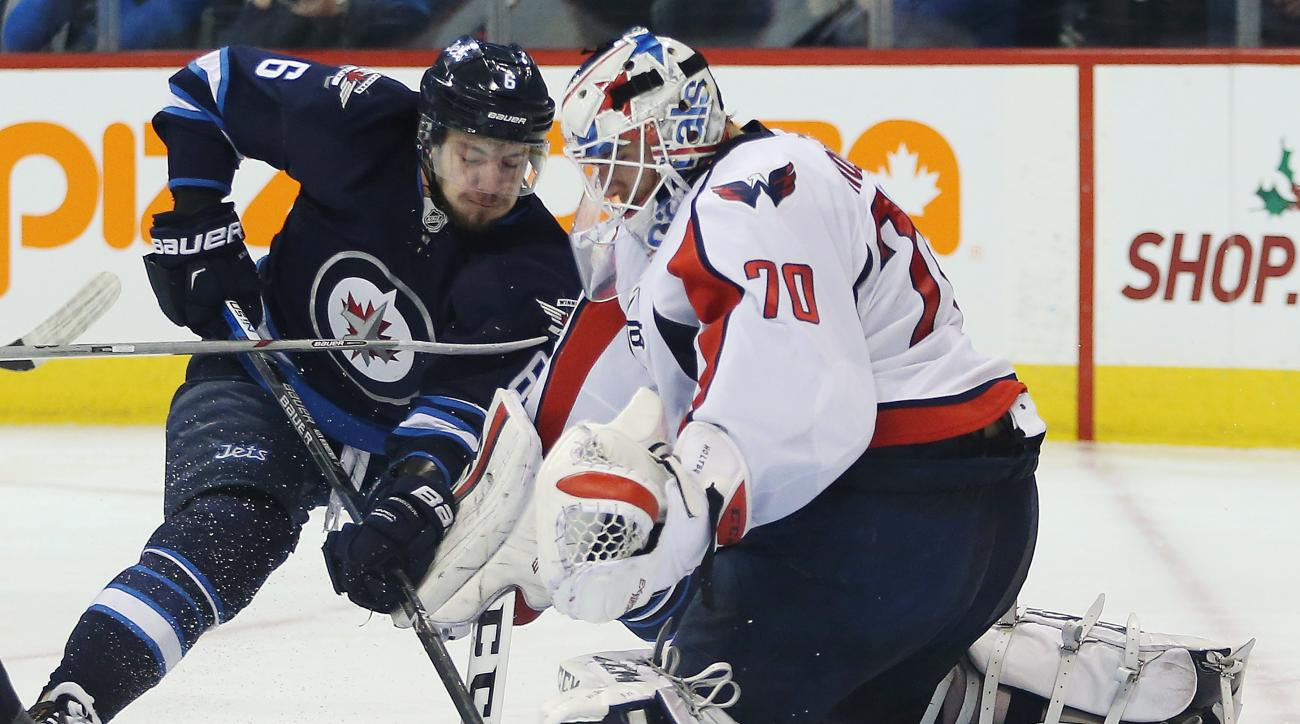 Winnipeg Jets' Alex Burmistrov (6) drives in on Washington Capitals goaltender Braden Holtby (70) during the second period of an NHL hockey game in Winnipeg, Manitoba on Saturday, Dec. 5, 2015. (John Woods/The Canadian Press via AP) MANDATORY CREDIT