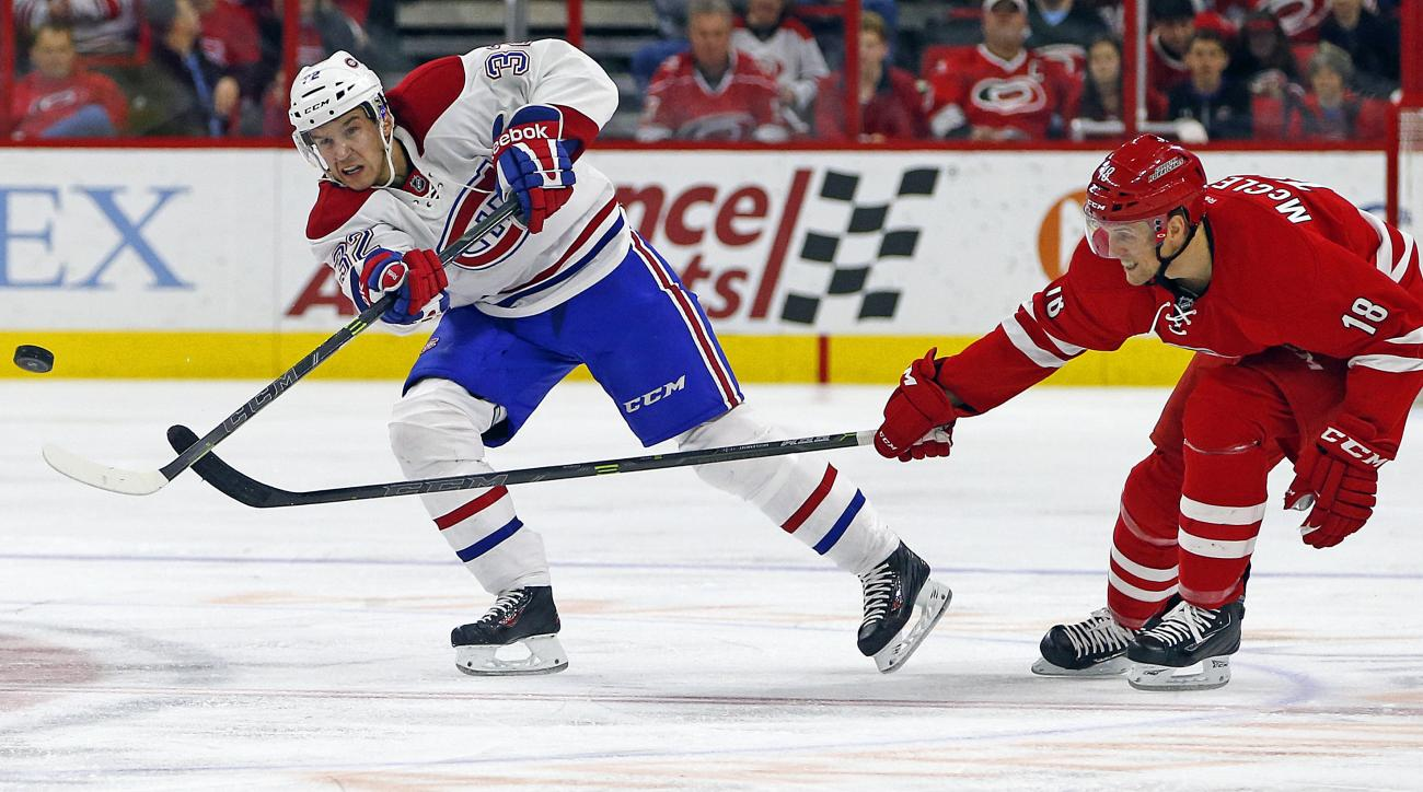 Montreal Canadiens' Brian Flynn (32) clears the puck in front of an advancing Carolina Hurricanes' Jay McClement (18) during the second period of an NHL hockey game, Saturday, Dec. 5, 2015, in Raleigh, N.C. (AP Photo/Karl B DeBlaker)