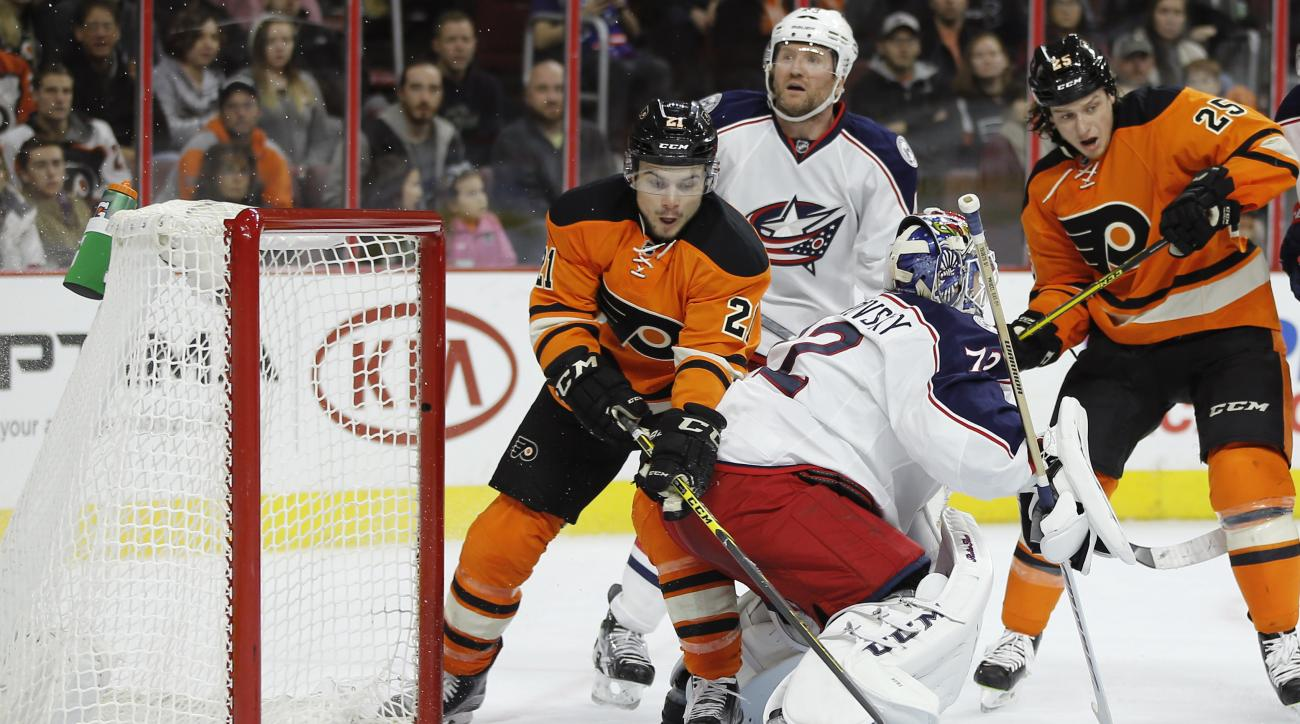 Philadelphia Flyers' Scott Laughton (21) tries to shoot a loose puck behind Columbus Blue Jackets' Sergei Bobrovsky (72) during the second period of an NHL hockey game, Saturday, Dec. 5, 2015, in Philadelphia. (AP Photo/Matt Slocum)