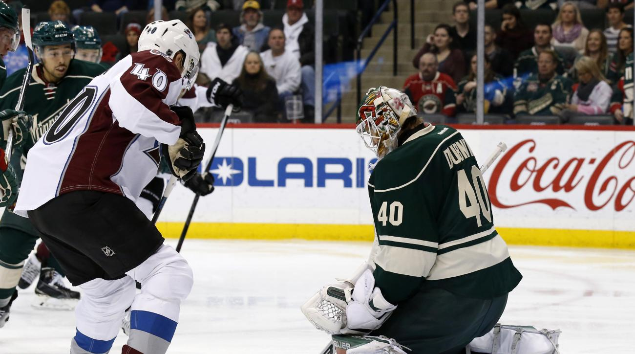 Minnesota Wild goalie Devan Dubnyk, right, deflects a shot in front of Colorado Avalanche left wing Alex Tanguay, left, during the second period of an NHL hockey game in St. Paul, Minn., Saturday, Dec. 5, 2015. (AP Photo/Ann Heisenfelt)