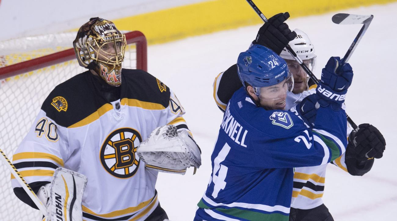 Boston Bruins defenseman Kevan Miller, right, tries to clear Vancouver Canucks right wing Adam Cracknell (24) from in front of Bruins goalie Tuukka Rask during the third period of an NHL hockey game Saturday, Dec. 5, 2015, in Vancouver, British Columbia.