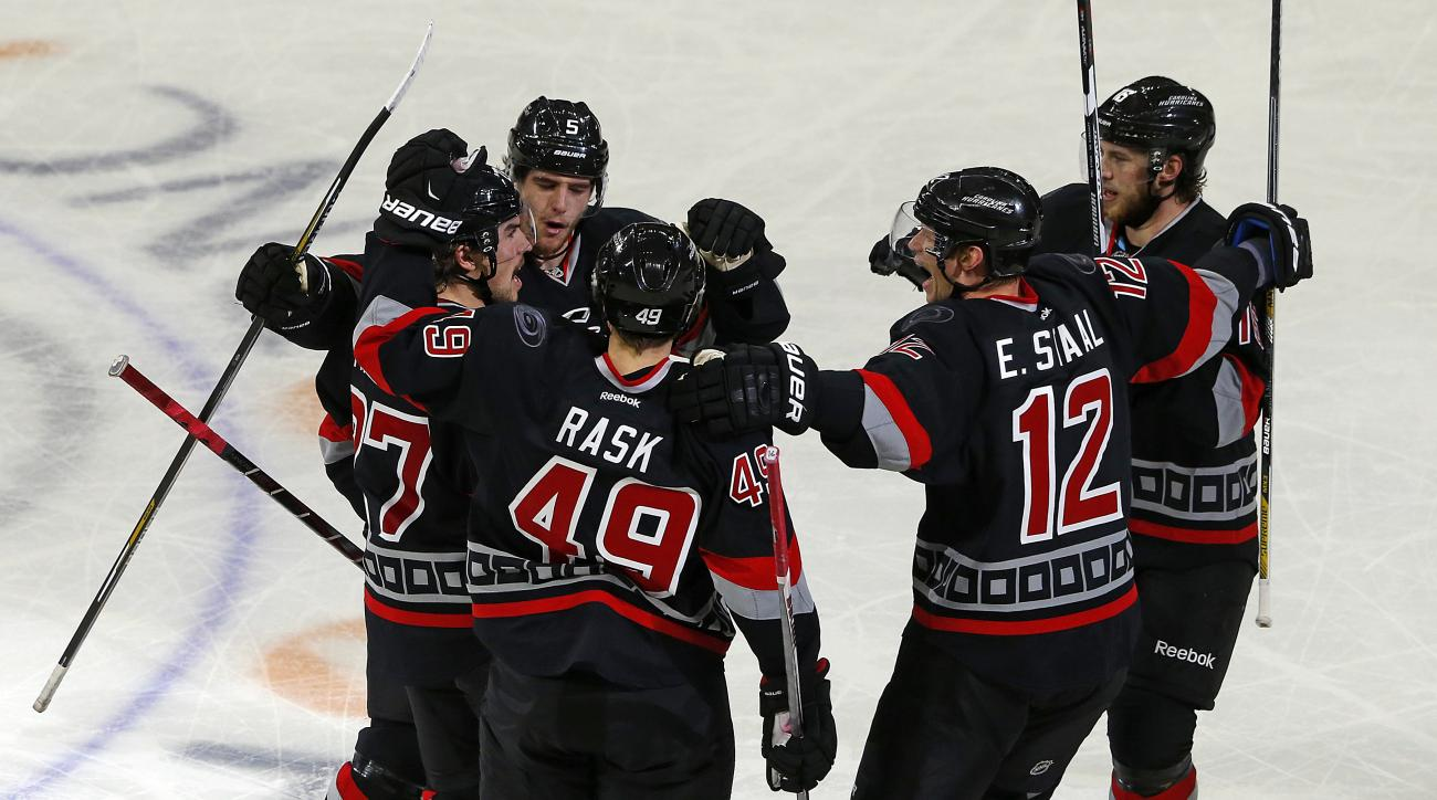 Carolina Hurricanes' Justin Faulk, left, is congratulated on his go ahead goal by teammates Noah Hanifin (5), Victor Rask (49), Eric Staal (12), and Elias Lindholm (16) of Sweden during closing minutes of the third period of an NHL hockey game against the