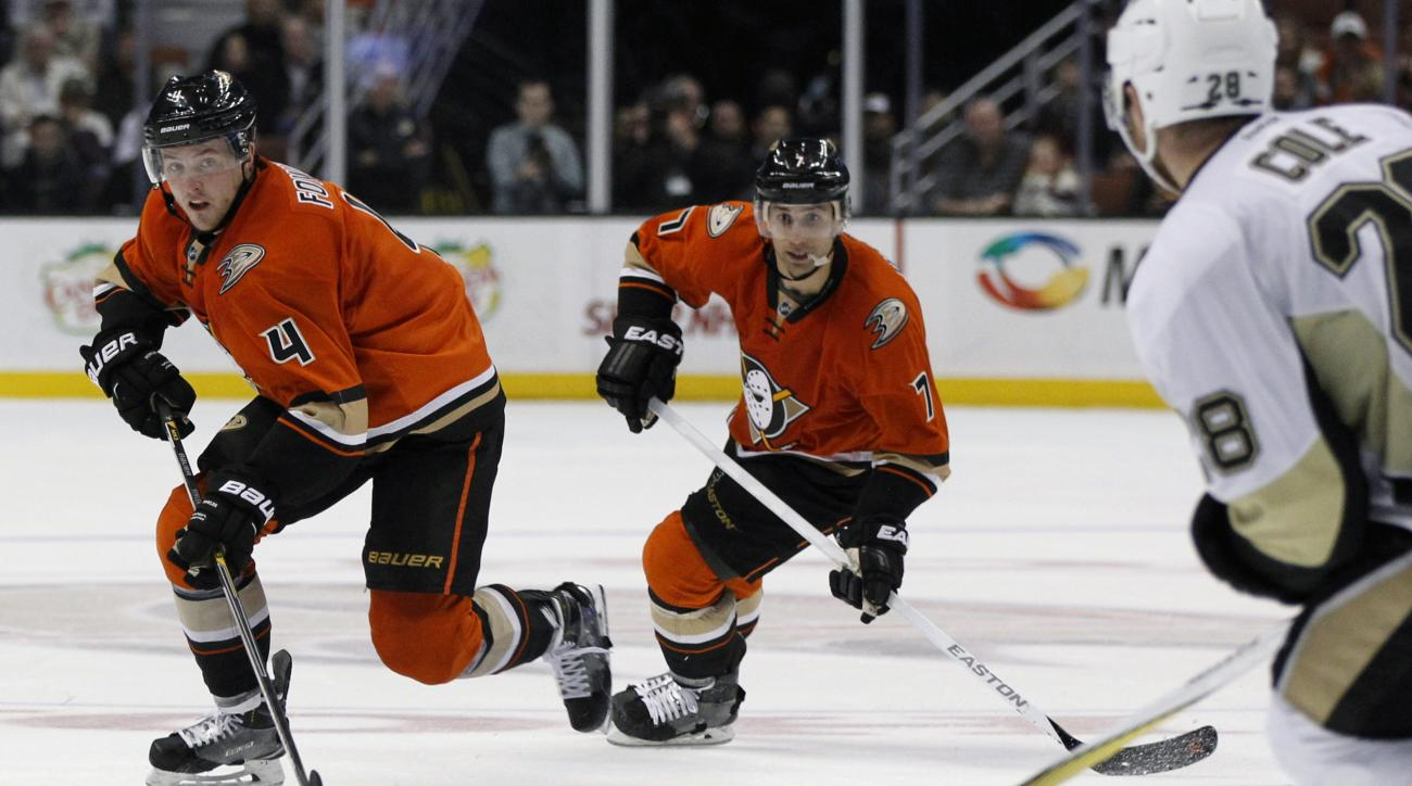 Anaheim Ducks defenseman Cam Fowler (4) controls the puck with center Andrew Cogliano (7) against Pittsburgh Penguins defenseman Ian Cole (28) during the second period of an NHL hockey game in Anaheim, Calif., Sunday, Dec. 6, 2015. (AP Photo/Alex Gallardo