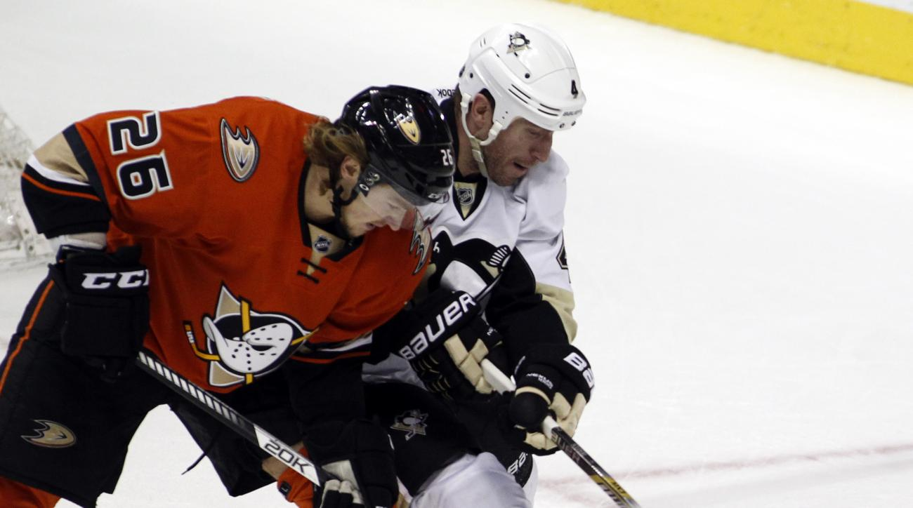 Anaheim Ducks left wing Carl Hagelin, left, battles Pittsburgh Penguins defenseman Rob Scuderi, right, for the puck during the third period of an NHL hockey game in Anaheim, Calif., Sunday, Dec. 6, 2015.  The Ducks won 2-1. (AP Photo/Alex Gallardo)