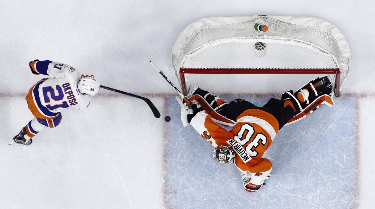 New York Islanders' Kyle Okposo, left, scores a goal against Philadelphia Flyers' Michal Neuvirth in a shootout during an NHL hockey game, Tuesday, Dec. 8, 2015, in Philadelphia. New York won 4-3 in a shootout. (AP Photo/Matt Slocum)