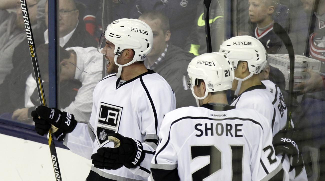 Los Angeles Kings' Alec Martinez, left, celebrates his overtime goal against the Columbus Blue Jackets with teammates Nick Shore (21) and Dustin Brown during an overtime period of an NHL hockey game in Columbus, Ohio, Tuesday, Dec. 8, 2015. Los Angeles wo