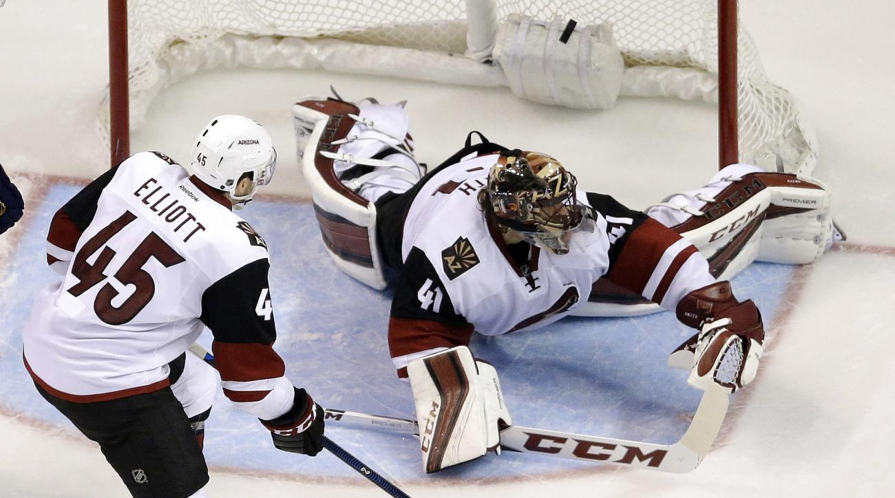 A shot by St. Louis Blues' Kevin Shattenkirk slips past Arizona Coyotes goalie Mike Smith, right, and Stefan Elliott, left, for a goal during the third period of an NHL hockey game, Tuesday, Dec. 8, 2015, in St. Louis. The Blues won 4-1. (AP Photo/Jeff Ro
