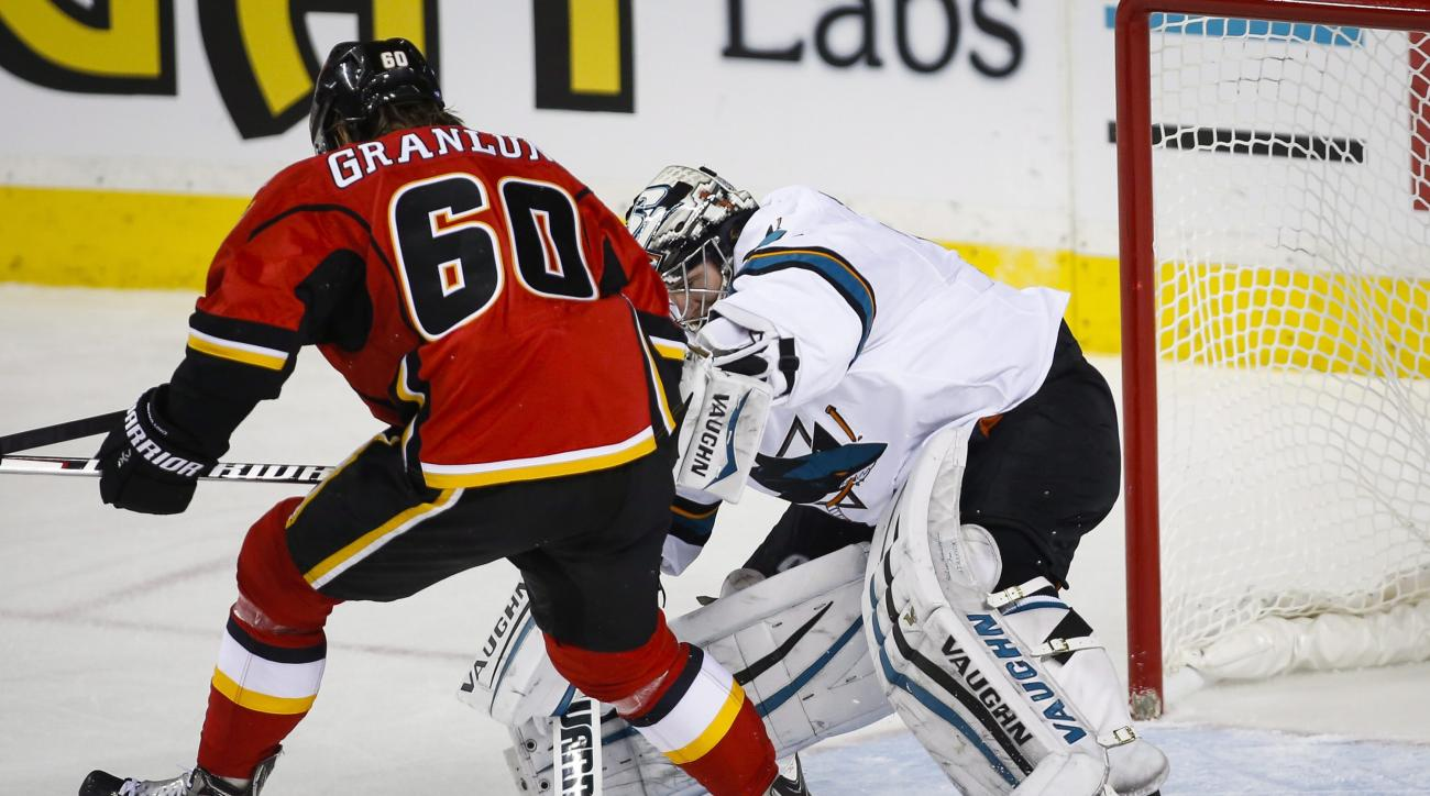 San Jose Sharks' goalie Alex Stalock, right, pokes the puck away from Calgary Flames' Markus Granlund during second period NHL hockey action, in Calgary, on Tuesday, Dec. 8, 2015. (Jeff McIntosh/The Canadian Press via AP)