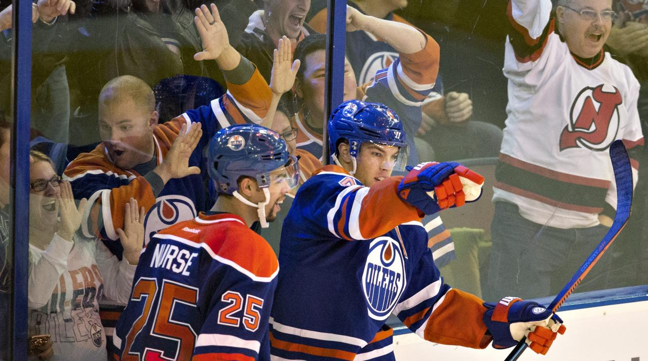 Edmonton Oilers' Darnell Nurse (25) and Taylor Hall (4) celebrate a goal on the San Jose Sharks during overtime an NHL hockey game in Edmonton, Alberta, Wednesday, Dec. 9, 2015. (Jason Franson/The Canadian Press via AP) MANDATORY CREDIT