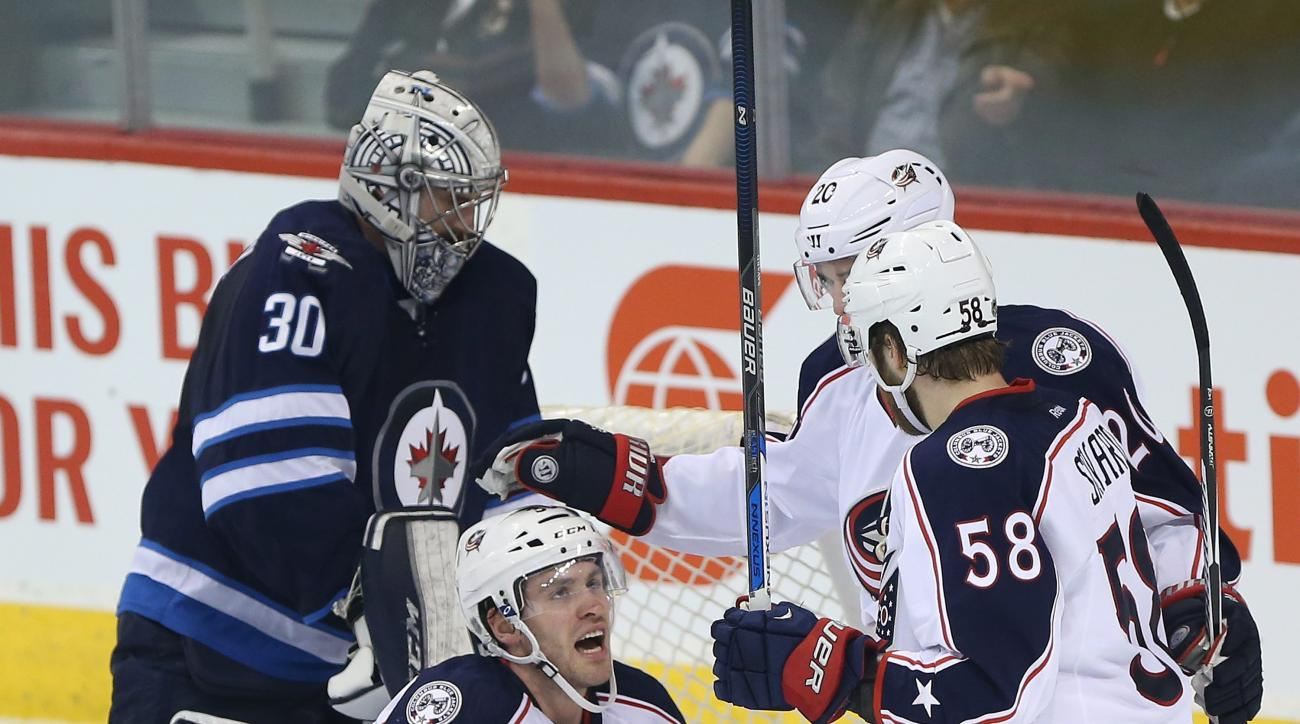 Columbus Blue Jackets' Boone Jenner (38), Brandon Saad (20) and David Savard (58) celebrate Jenner's goal against Winnipeg Jets' goaltender Connor Hellebuyck (30) during the first period of an NHL hockey game in Winnipeg, Manitoba, Thursday, Dec. 10, 2015