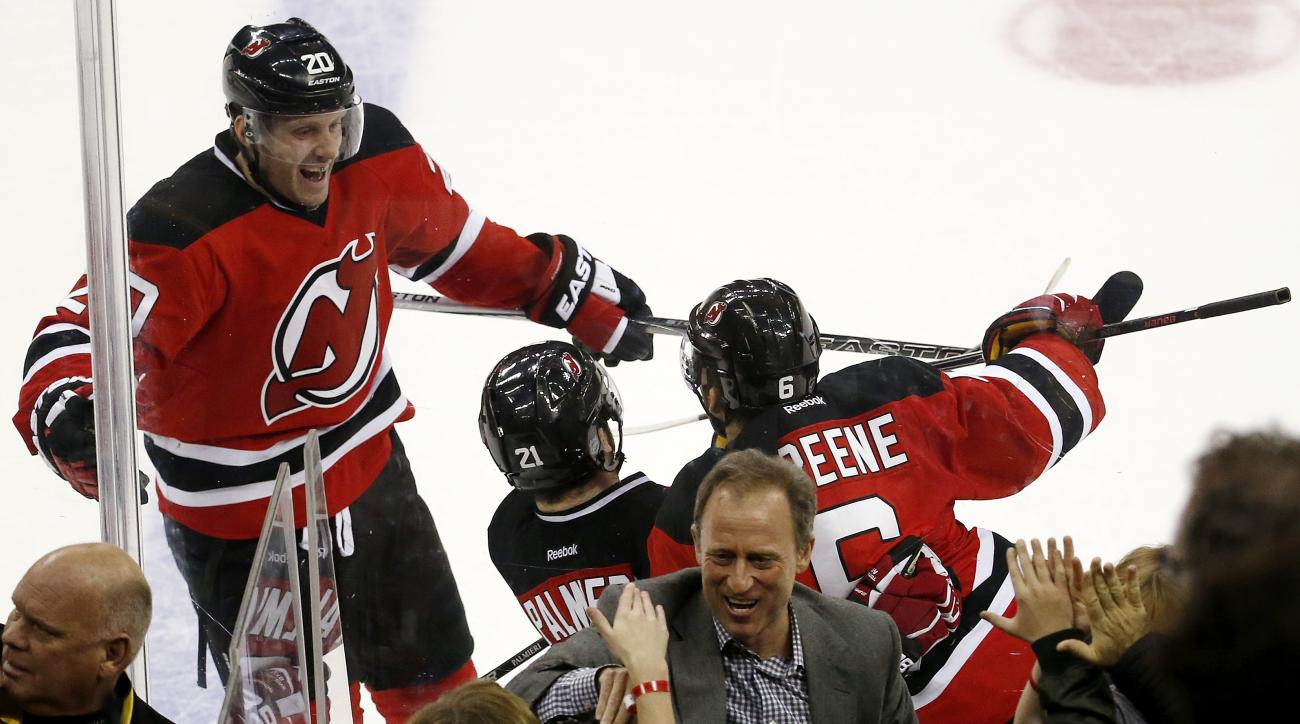 New Jersey Devils owner Josh Harris, center, high-fives people as right wing Lee Stempniak (20), right wing Kyle Palmieri (21) and defenseman Andy Greene (6) celebrate Palmieri's overtime goal against the Detroit Red Wings in an NHL game, Friday, Dec. 11,