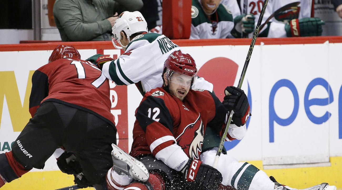 Arizona Coyotes' Brad Richardson (12), Steve Downie (17) and Minnesota Wild's Nino Niederreiter (22), of Switzerland, collide as they all go after the puck during the second period of an NHL hockey game Friday, Dec. 11, 2015 in Glendale, Ariz. (AP Photo/R