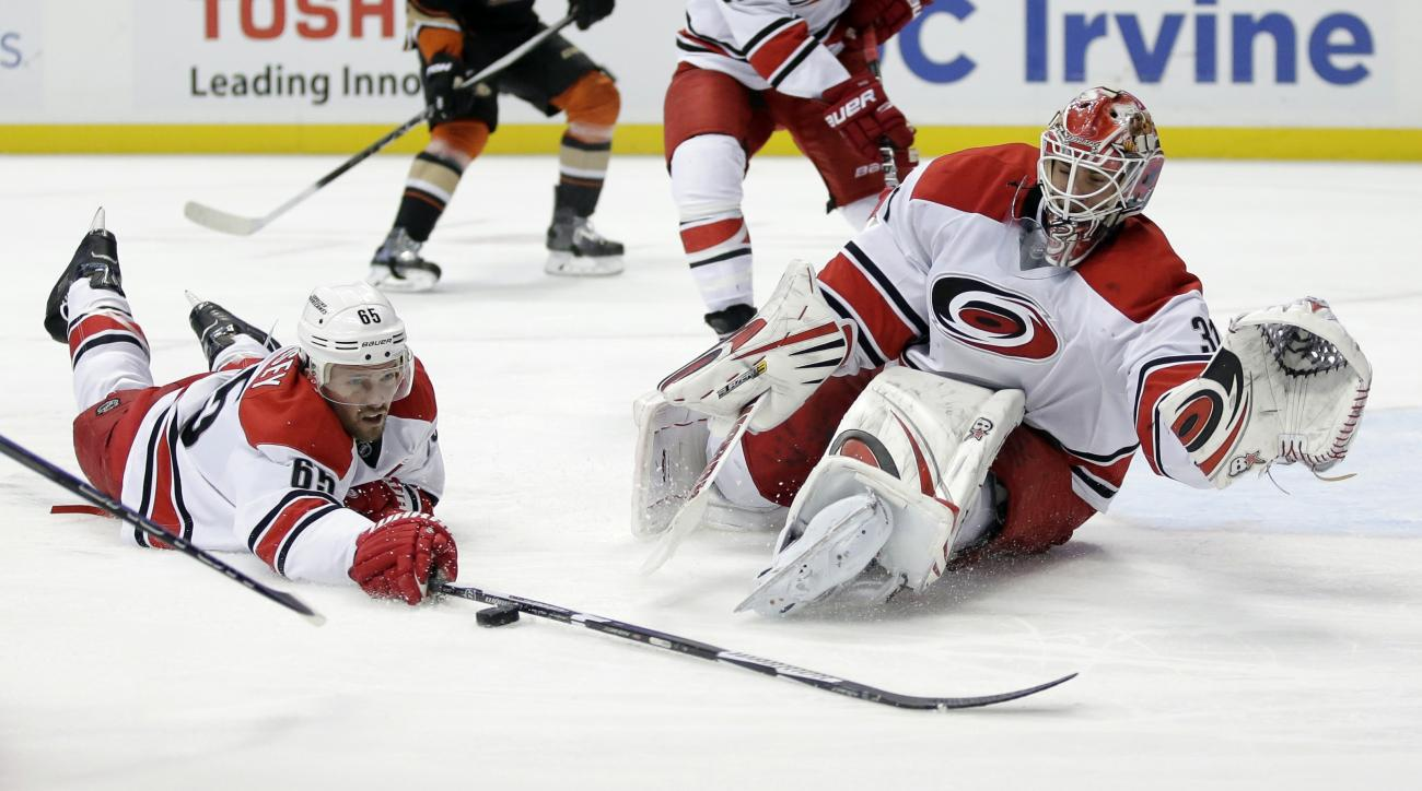 Carolina Hurricanes defenseman Ron Hainsey, left, blocks a shot as goalie Eddie Lack looks during the second period of an NHL hockey game against the Anaheim Ducks in Anaheim, Calif., Friday, Dec. 11, 2015. (AP Photo/Chris Carlson)