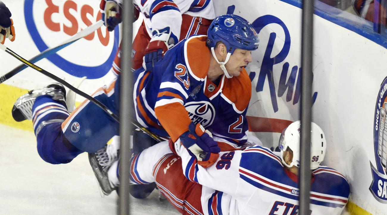 Edmonton Oilers' Matt Hendricks (23) falls on New York Rangers' Emerson Etem during the second period of an NHL hockey game in Edmonton, Alberta, on Friday, Dec. 11, 2015. (John Ulan/The Canadian Press via AP) MANDATORY CREDIT