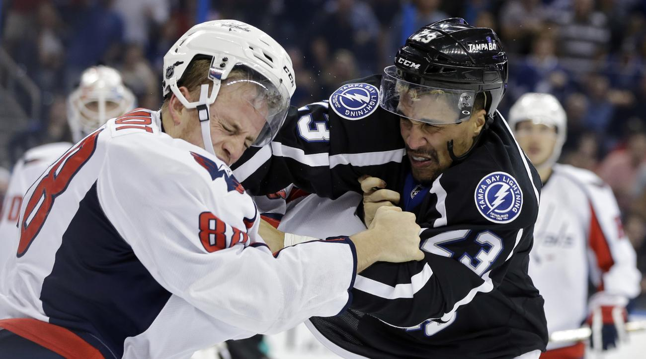 Tampa Bay Lightning right wing J.T. Brown (23) punches Washington Capitals defenseman Nate Schmidt in the face as they fight during the second period of an NHL hockey game Saturday, Dec. 12, 2015, in Tampa, Fla. Both players got 5-minute major penalties.