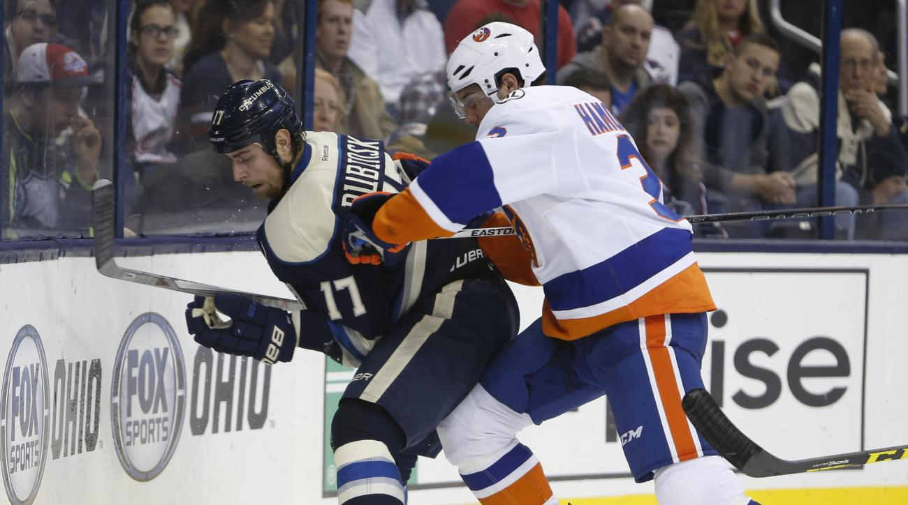 New York Islanders' Travis Hamonic, right, checks Columbus Blue Jackets' Brandon Dubinsky during the second period of an NHL hockey game Saturday, Dec. 12, 2015, in Columbus, Ohio. The Islanders beat the Blue Jackets 3-2 in overtime. (AP Photo/Jay LaPrete