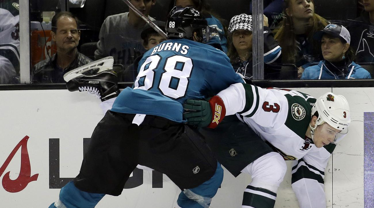 Minnesota Wild's Charlie Coyle (3) is pressed against the boards by San Jose Sharks' Brent Burns (88) during the second period of an NHL hockey game Saturday, Dec. 12, 2015, in San Jose, Calif. (AP Photo/Marcio Jose Sanchez)