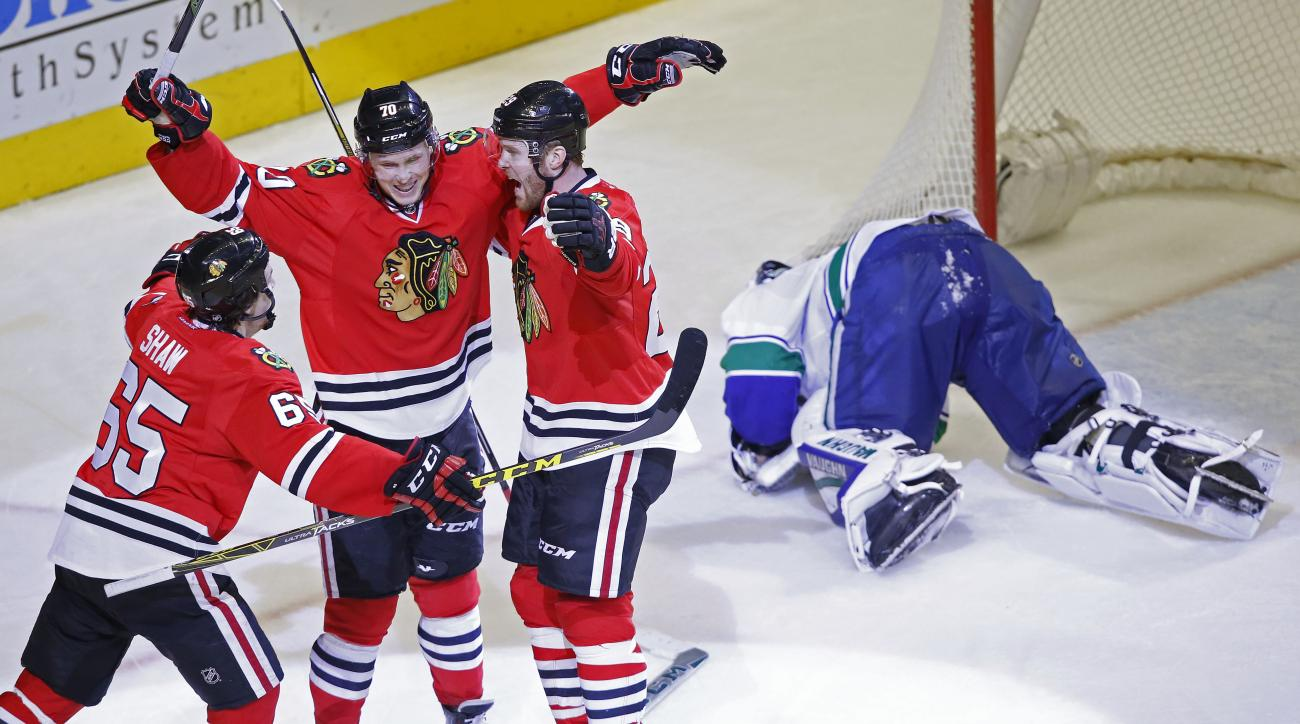 Chicago Blackhawks center Dennis Rasmussen (70) celebrates his goal past Vancouver Canucks goalie Ryan Miller (30) with teammates Andrew Shaw (65) and Bryan Bickell (29) during the third period of an NHL hockey game in Chicago, Sunday, Dec. 13, 2015. Chic