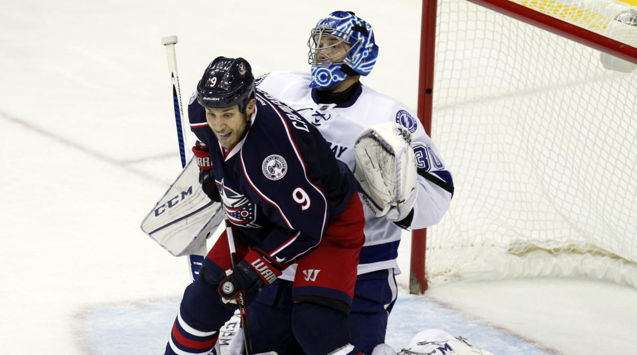 Columbus Blue Jackets' Gregory Campbell, left, works for the puck against Tampa Bay Lightning goalie Ben Bishop during the third period of an NHL hockey game in Columbus, Ohio, Monday, Dec. 14, 2015. Tampa Bay won 2-1. (AP Photo/Paul Vernon)