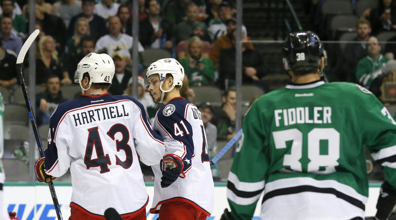 Columbus Blue Jackets' Scott Hartnell (43) is congratulated by Alexander Wennberg (41) after scoring against the Dallas Stars, as Vernon Fiddler (38) watches during the second period of an NHL hockey game, Tuesday, Dec. 15, 2015, in Dallas. (AP Photo/Tony