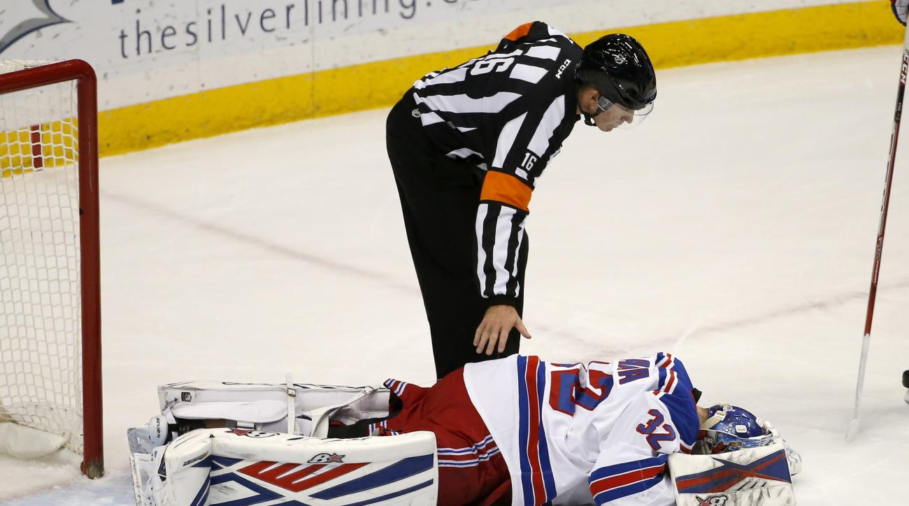 Official Brian Pochmara checks on New York Rangers goalie Antti Raanta after Raanta took a puck to the forehead during the first period of an NHL hockey game against the Minnesota Wild in St. Paul, Minn., Thursday, Dec. 17, 2015. Raanta left the game. (AP